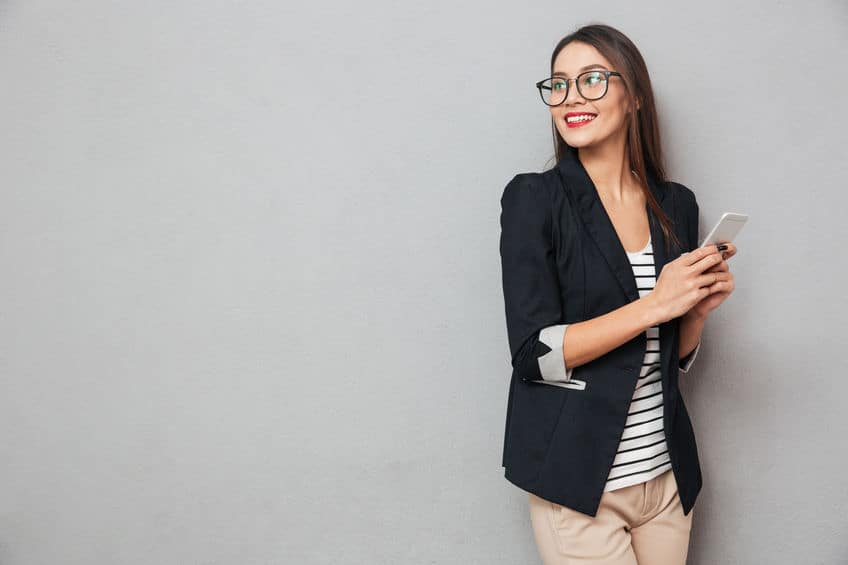 Smiling asian business woman in eyeglasses holding smartphone and looking back over gray background